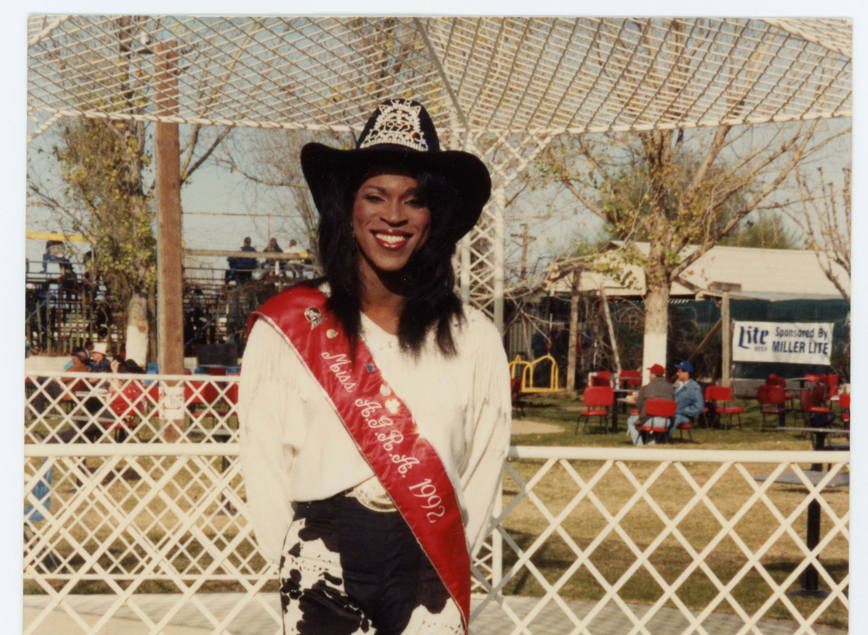 Miss Arizona Gay Rodeo Association posing with pageant sash; 1992