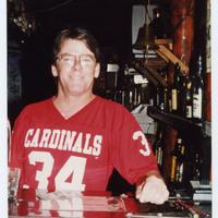 Man posing behind bar