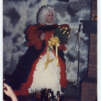 Drag performer on stage with bouquet