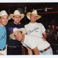 Four men wearing cowboy hats